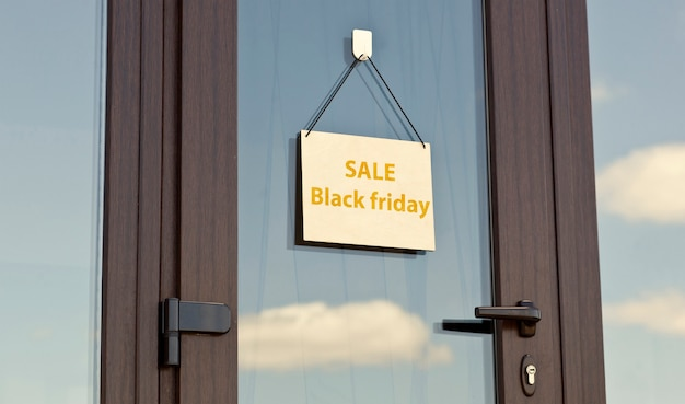 The wooden sign with text sale black friday hanging on the door in the store