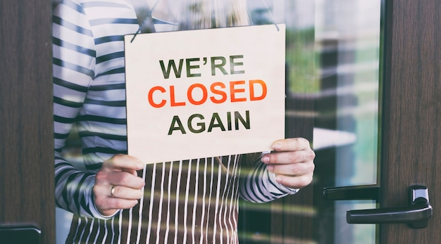 The wooden sign with text: sorry, we're closed again hanging on the door in cafe