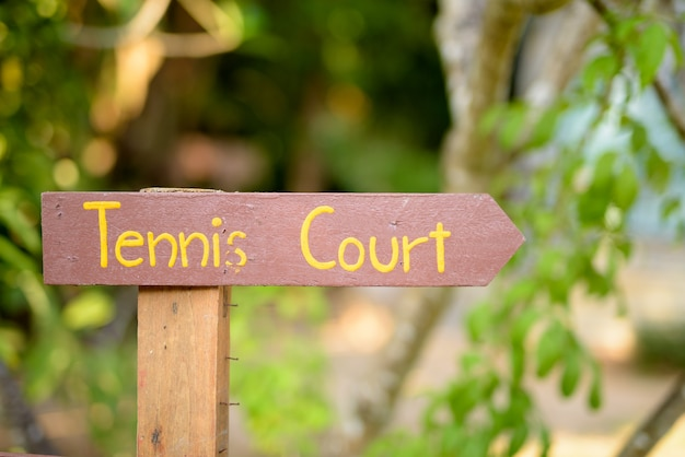 テニスコートを指す木製の道標