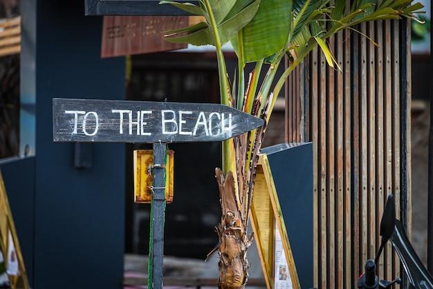 カフェとヤシの木のある観光通りのビーチに碑文が刻まれた木製の道標