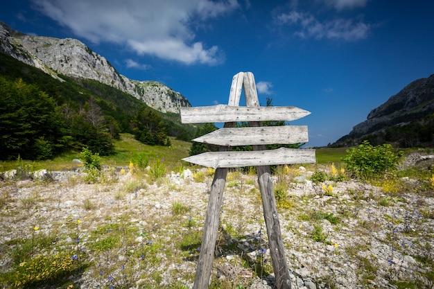 Деревянный указатель с тремя направлениями у подножия большой горы