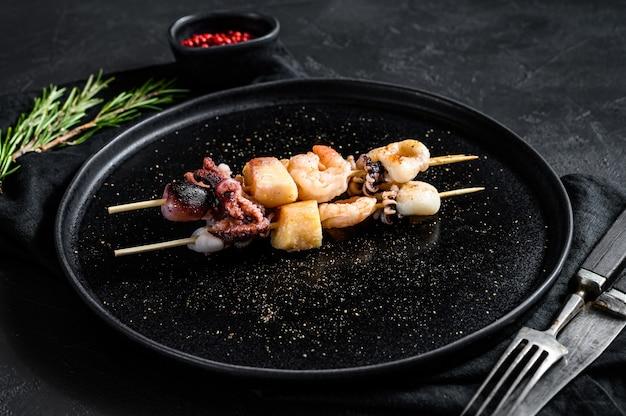 Деревянные шпажки с креветками, осьминогом, кальмарами и мидиями. кебаб с морепродуктами. черная стена. вид сверху
