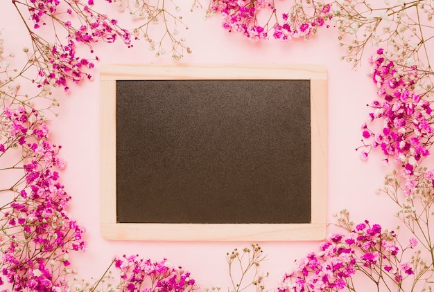 Wooden slate decorated with baby's-breath flowers on pink background