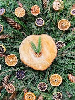 말린 오렌지 조각과 원뿔로 장식된 녹색 전나무 나뭇가지에 있는 나무 조각. 크리스마스와 새 해 빈티지 겨울 휴가 축제 구성입니다.