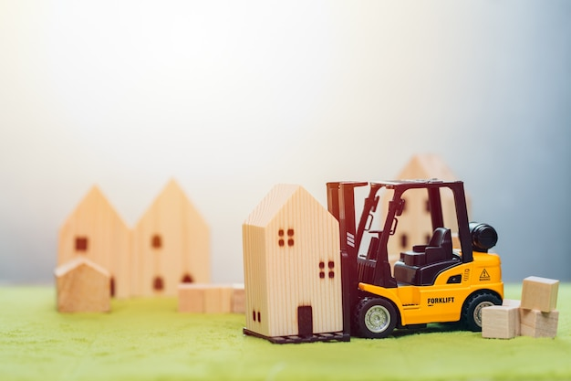 Wooden small home model with forklift car for moving house or home building renovation for good community concept