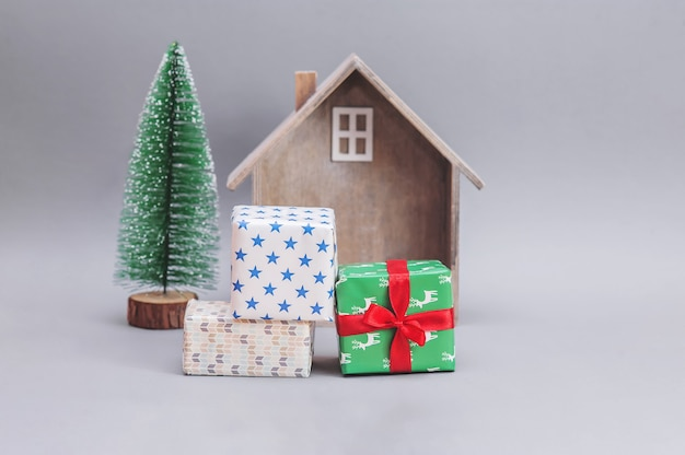 Деревянный домик с подарками и рождественской елкой на сером фоне. новогодняя композиция. рождественские подарки.