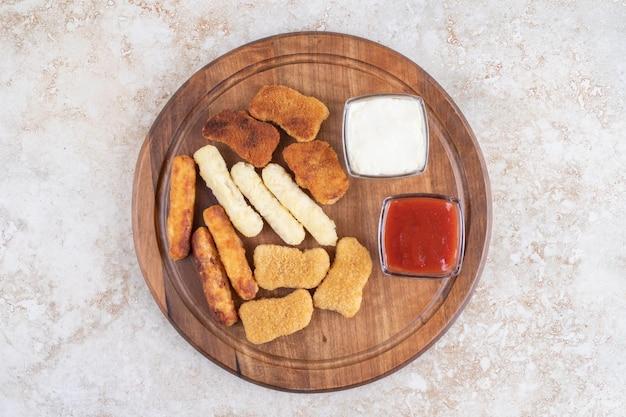 Tagliere in legno con bocconcini di pollo, bastoncini di formaggio, salsicce alla griglia e salse intorno.