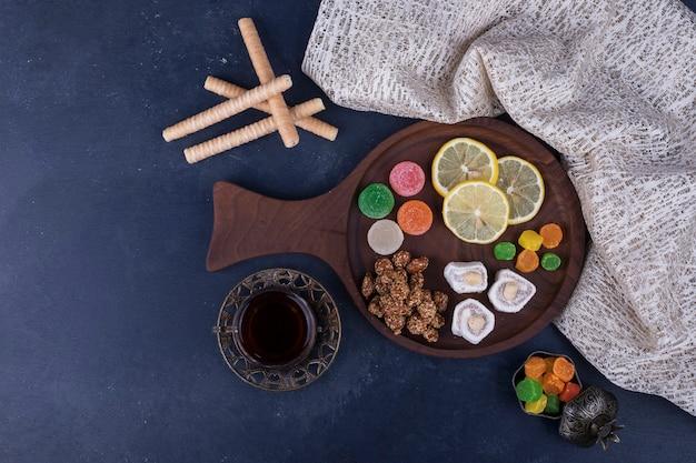 Деревянная закуска с конфетами и стаканом чая на кухонном полотенце