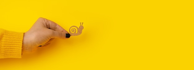 Wooden snail in hand over yellow background, slowness concept, panoramic mock-up