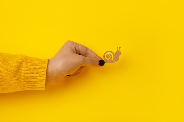 Wooden snail in hand over yellow background, slowness concept