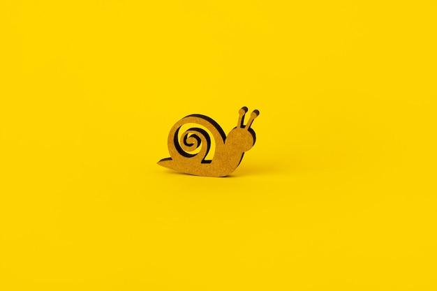 黄色の上の木製のカタツムリ、低速または土地の概念