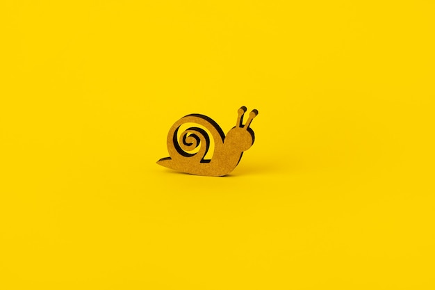 Wooden snail over yellow, concept of low speed or land