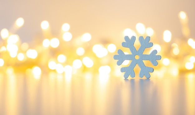 Wooden snowflake close up on a golden background with bokeh.