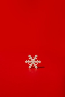 Wooden snowflake on red table