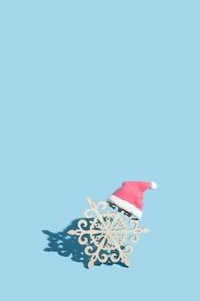 Wooden snowflake in santa hat on blue background: new year minimal concept
