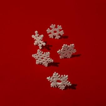 Fiocchi di neve in legno sulla tavola rossa