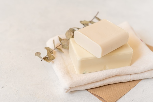 Wooden soap dish, craft paper, cotton fabric, soap, over white background.