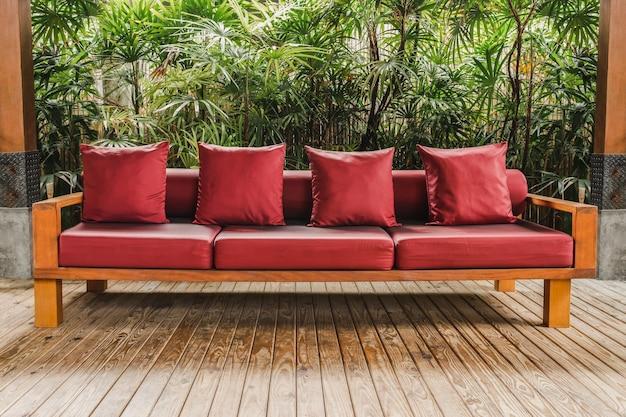 Деревянный диван с красной подушкой на деревянном полу в саду.