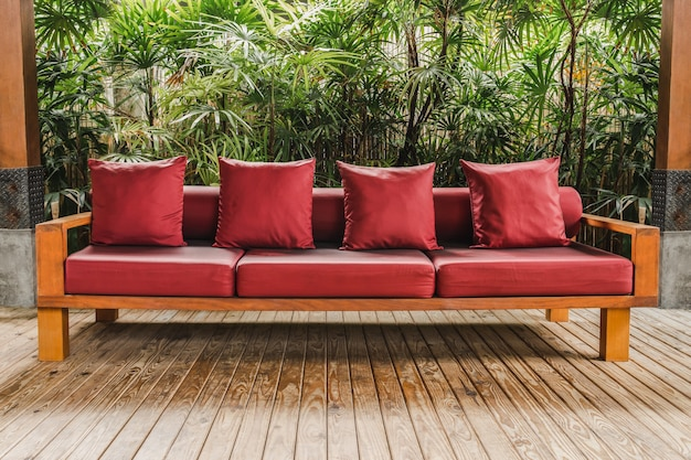 Wooden sofa with red cushion on wooden floor in garden.