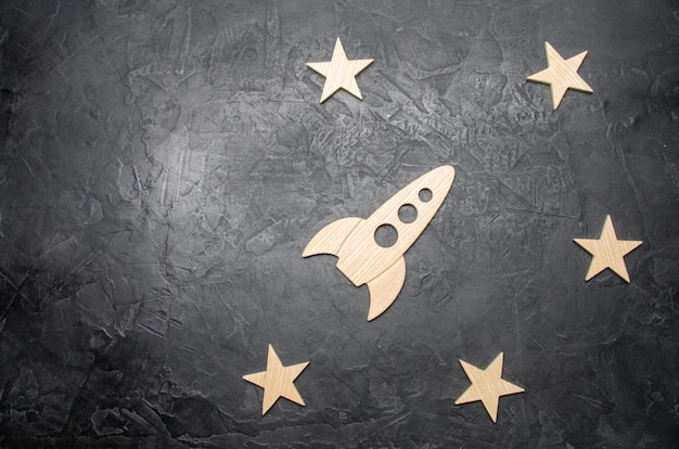 Wooden space rocket and stars on a dark background. education and popular science.