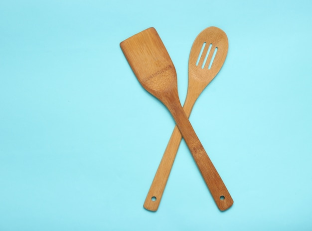 Wooden spatula for cooking on blue table. kitchen concept, minimalism