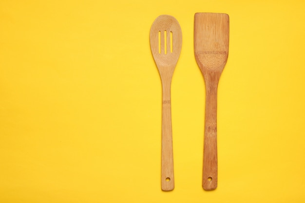 Wooden spatula for cooking on a yellow table. kitchen concept, minimalism
