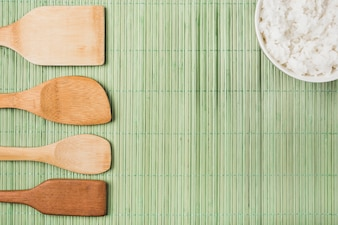 Wooden spatulas and cooked rice bowl on green placemat