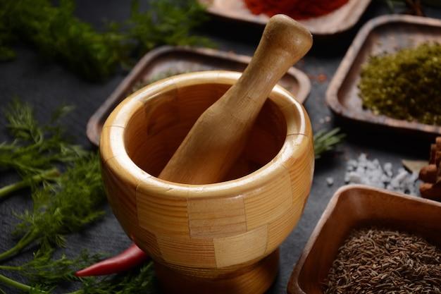 木製のスパイス乳鉢と暗い背景のスパイス