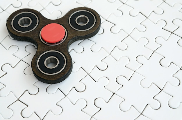 A wooden spinner lies on a white jigsaw puzzle background