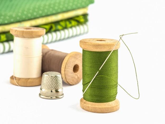 Деревянная катушка с ниткой вышитая тканью на белом фоне