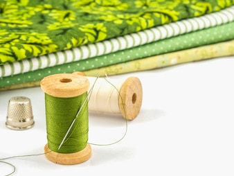Wooden spool of thread embroidery set with cloth over white background
