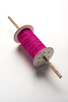 흰색 배경 위에 격리된 분홍색 또는 흰색 스레드가 있는 나무 스풀 또는 차크리 또는 릴 또는 fikri