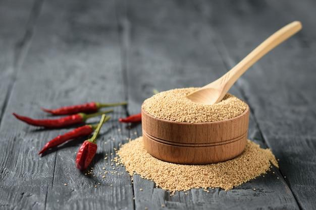 木のスプーンとボウルにアマランスの種子と唐辛子を木製のテーブル。