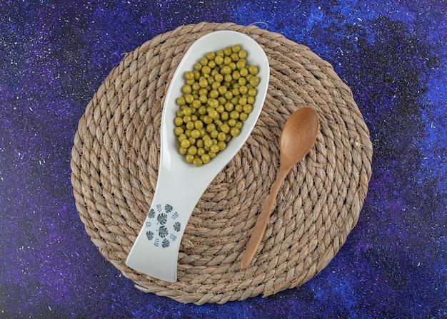 木のスプーンとセラミックボウルにエンドウ豆のマリネをたっぷり。
