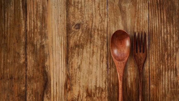 木製の背景に木のスプーンとフォーク。アジアンスタイルの木製家電。コピースペース