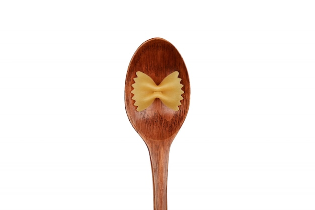木のスプーンと弓の形のパスタ