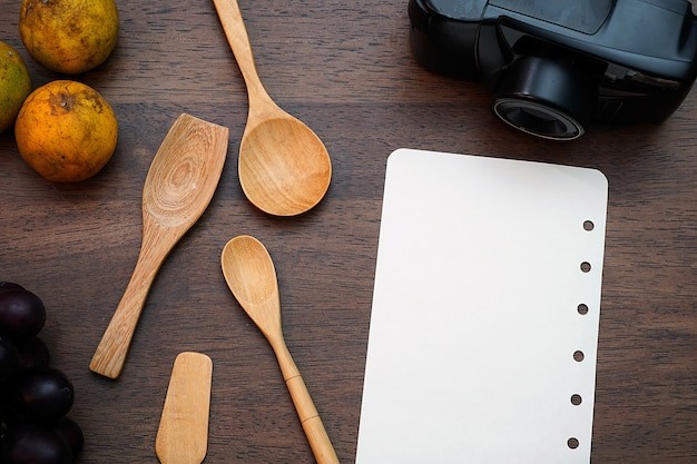 Wooden spoon and blank page on wooden table