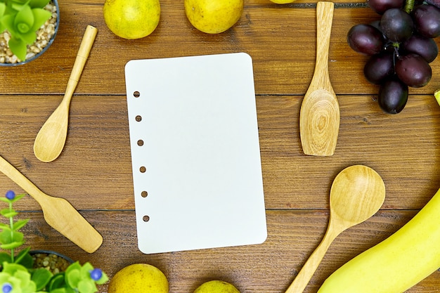 Wooden spoon and blank recipe book on wooden table