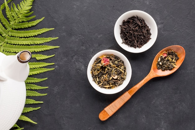 Wooden spoon and ceramic bowl of tea herb on black surface