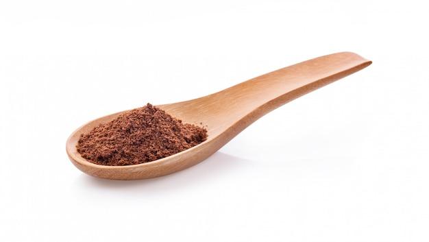白い背景で隔離のコーヒーパウダーで満たされた木のスプーン