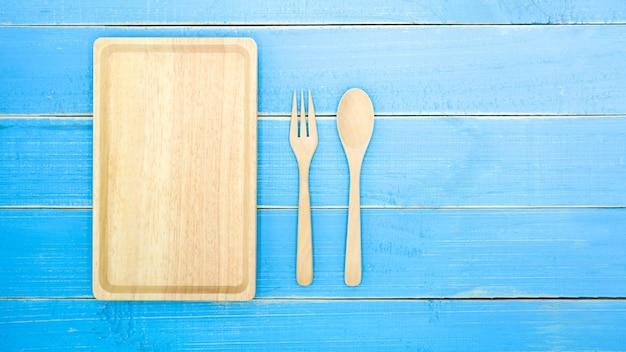 오래 된 푸른 나무 책상 배경에 나무 숟가락, 포크와 접시