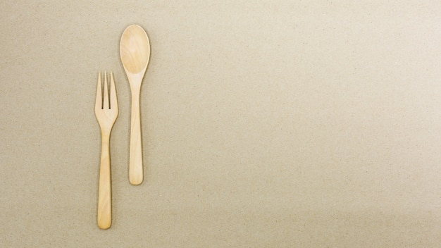 Wooden spoon and fork on brown paper - background