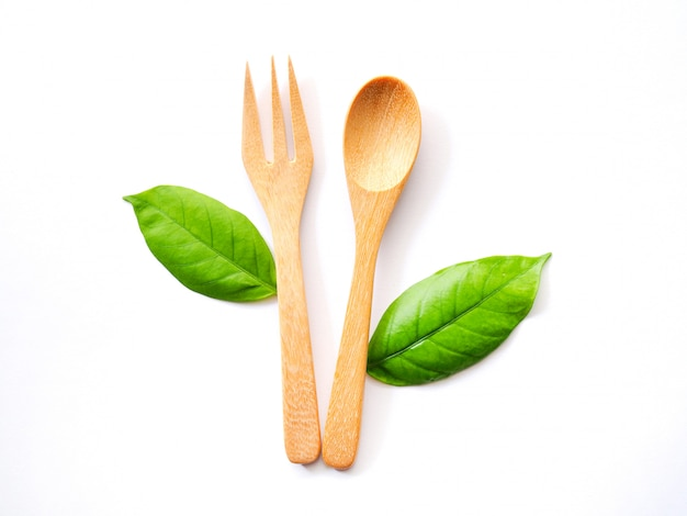 Wooden spoon and fork and green leaf, natural wooden utensils eco-friendly and safe for health.