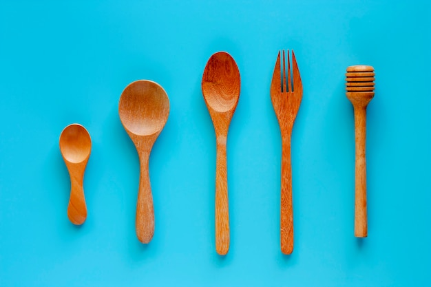 Wooden spoon, fork and honey dipper on blue background