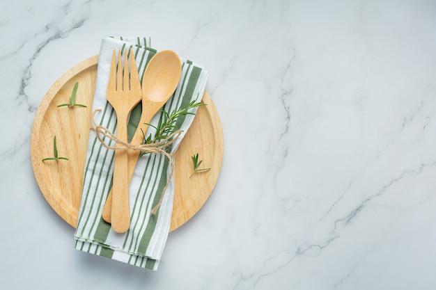 Cucchiaio di legno e forchetta con piante di rosmarino sul piatto di legno