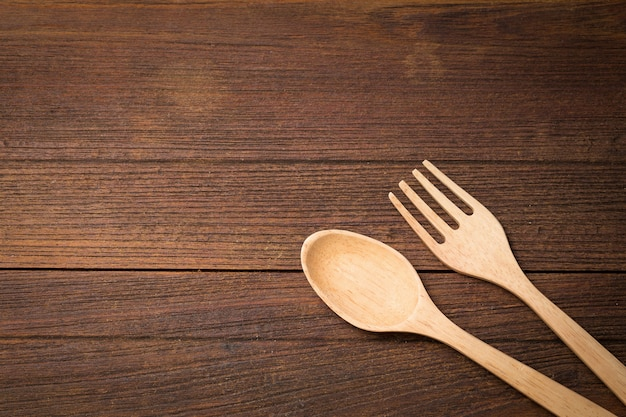 Wooden spoon and fork on wooden background.
