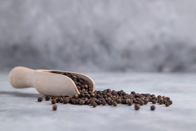A wooden spoon full of black pepper corns placed on stone table . high quality photo