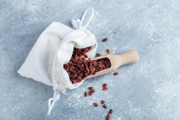 Un cucchiaio di legno pieno di mirtilli rossi secchi.