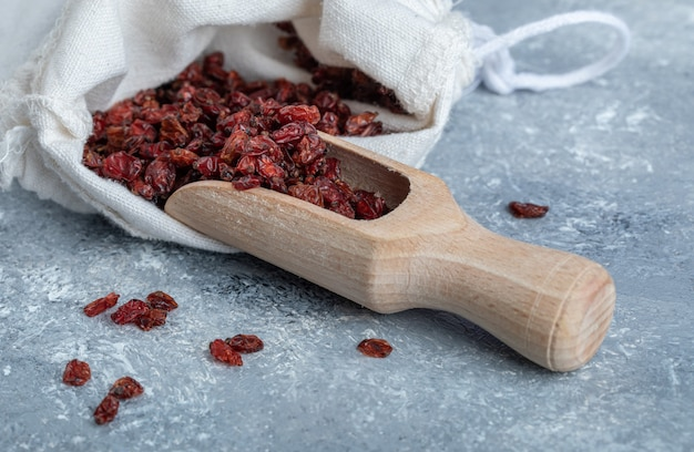 A wooden spoon full of dried cranberries.