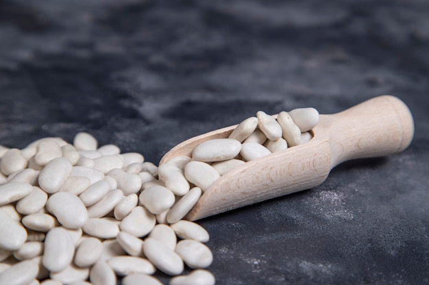 A wooden spoon full of dry butter beans placed on stone